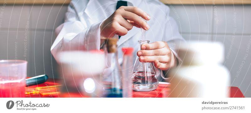 Ernsthaftes Kind beim Spielen mit chemischen Flüssigkeiten Flasche Tisch Wissenschaften Klassenraum Tafel Labor Internet Mensch Junge Kindheit Hand authentisch