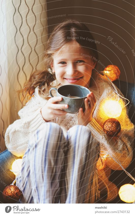 Kind Mädchen trinkt heißen Kakao zu Hause im Winter trinken Tee Leben Erholung Dekoration & Verzierung Stuhl Feste & Feiern Weihnachten & Advent Kindheit sitzen