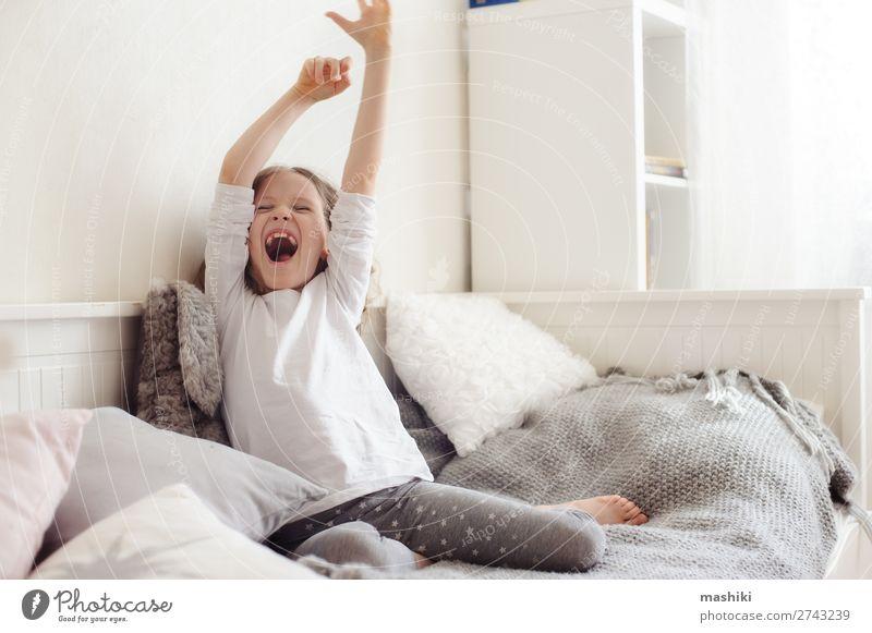 fröhlich schläfriges Kind Mädchen, das sich in ihrem Zimmer ausdehnt. Lifestyle Freude Glück Erholung Spielen Schlafzimmer Kindheit Spielzeug Teddybär Lächeln