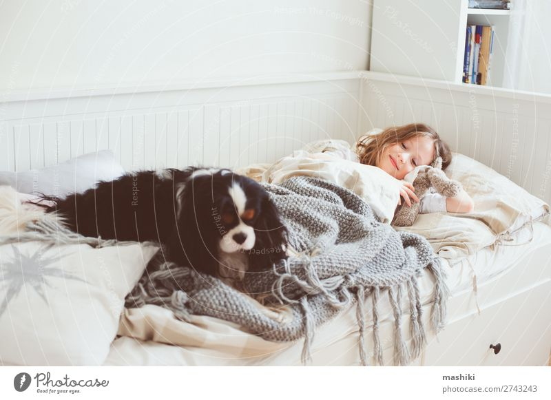 glückliches Kind Mädchen, das morgens aufwacht. Lifestyle Freude Glück Erholung Spielen Schlafzimmer Freundschaft Kindheit Haustier Hund Lächeln lachen schlafen