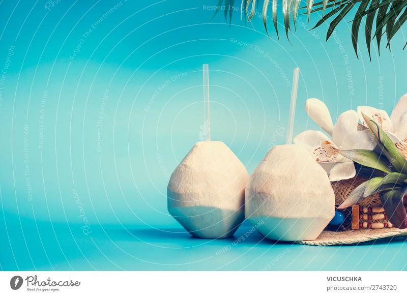 Frischer tropischer Kokosnuss-Cocktail mit Trinkhalmen und Palmblättern und Blumen auf blau-türkisem Hintergrund. Tropischer Sommerurlaub, Reise- und Ferienkonzept