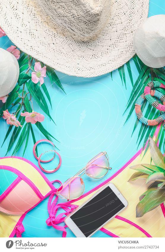 Draufsicht auf weibliche Strandaccessoires im Hintergrund mit tropischen Blättern und Blumen, Sonnenbrille und Strohhut, Bikini und Smartphone auf Sonnenblau. Konzept für den Sommerurlaub