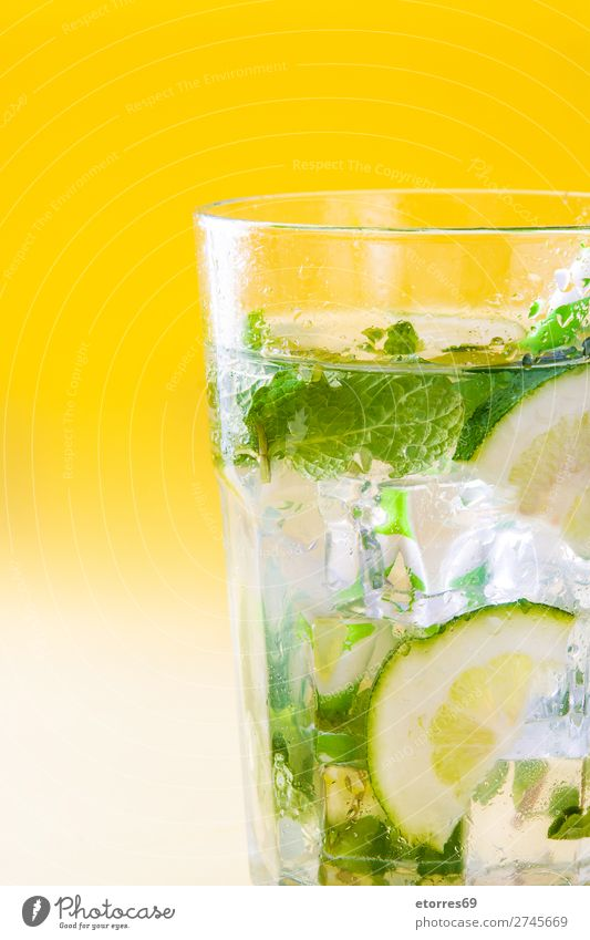 Mojito-Cocktail im Glas auf gelbem Hintergrund. Getränk trinken Alkohol Erfrischung Sommer Kalk grün Minze Saft Rum kalt Eis Mixer Frucht Zutaten Zucker