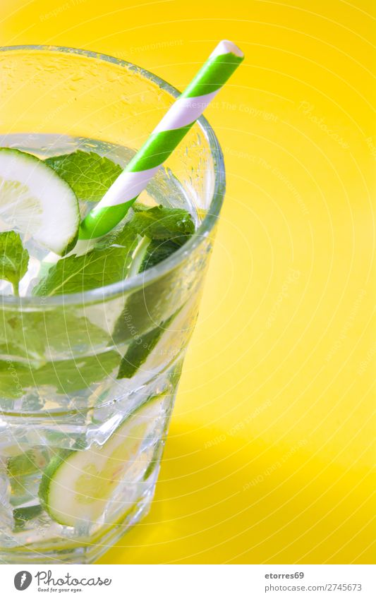 Mojito-Cocktail im Glas auf gelbem Hintergrund Getränk trinken Alkohol Erfrischung Sommer Kalk grün Minze Saft Rum kalt Eis Speiseeis Mischmaschine Frucht