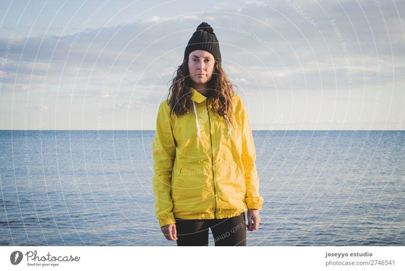 Frau am Strand im Winter Lifestyle Leben Erholung Ausflug Freiheit Sonne Sport Sitzung 30-45 Jahre Erwachsene Natur Horizont Küste Mode Jacke Mantel Hut gelb