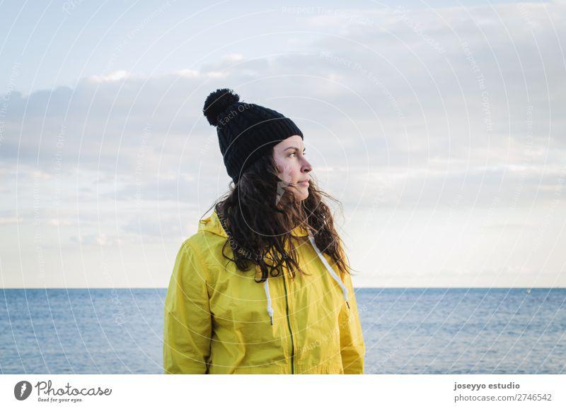 Brünette Frau am Strand Lifestyle Leben Erholung Ausflug Freiheit Sonne Winter Sport Sitzung 30-45 Jahre Erwachsene Natur Horizont Küste Mode Jacke Mantel Hut