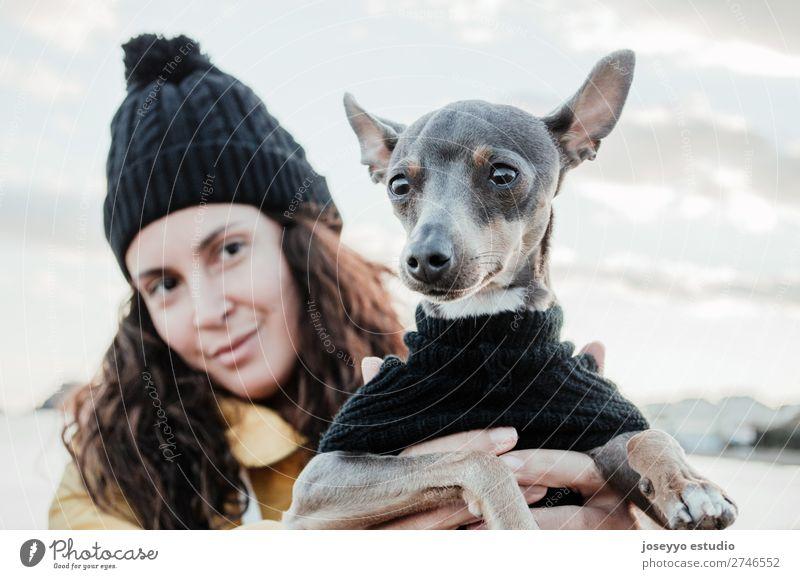 Frau mit ihrem kleinen Hund Lifestyle Erholung Ausflug Freiheit Winter Freundschaft Erwachsene Natur Tier Jacke Mantel Hut Haustier Liebe kuschlig gelb