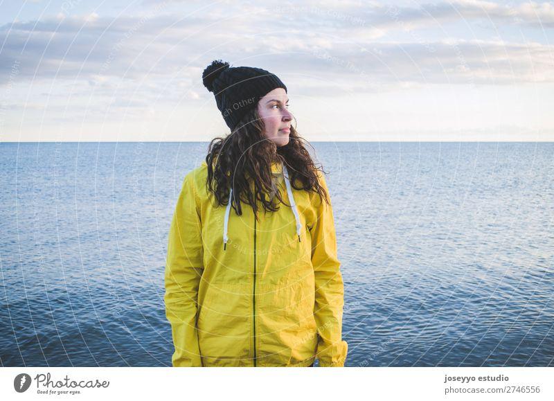 Junge Frau am Strand im Winter Lifestyle Leben Erholung Ausflug Freiheit Sonne Sport Sitzung 30-45 Jahre Erwachsene Natur Horizont Küste Mode Jacke Mantel Hut