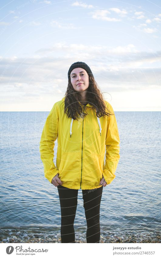 Junge Frau am Strand Lifestyle Leben Erholung Ausflug Freiheit Sonne Winter Sport Sitzung 30-45 Jahre Erwachsene Natur Horizont Küste Platz Mode Jacke Mantel