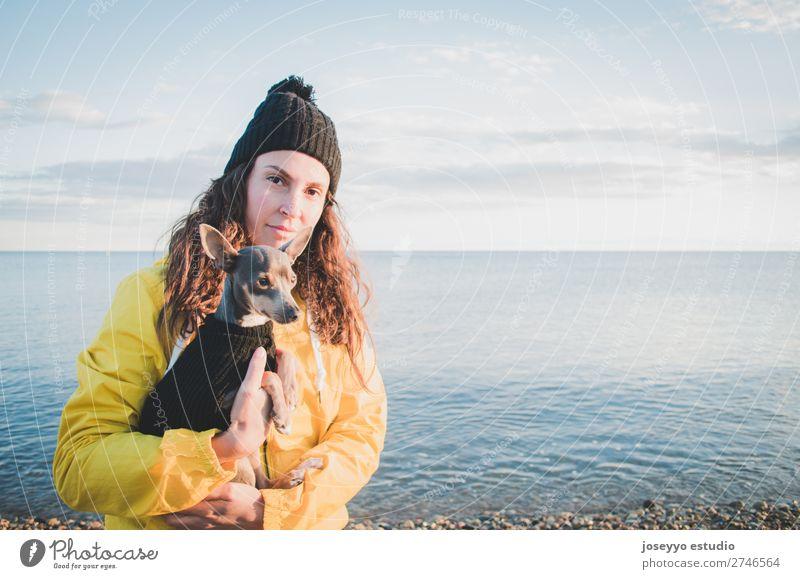 Frau mit ihrem kleinen Hund am Strand Lifestyle Erholung Ausflug Freiheit Sonne Winter Freundschaft 30-45 Jahre Erwachsene Natur Tier Horizont Küste Jacke