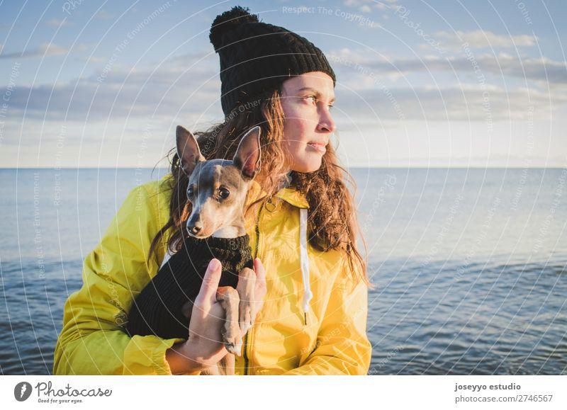 Frau mit ihrem kleinen Hund am Strand Lifestyle Ausflug Freiheit Sonne Winter Freundschaft 30-45 Jahre Erwachsene Natur Tier Horizont Küste Jacke Mantel Hut