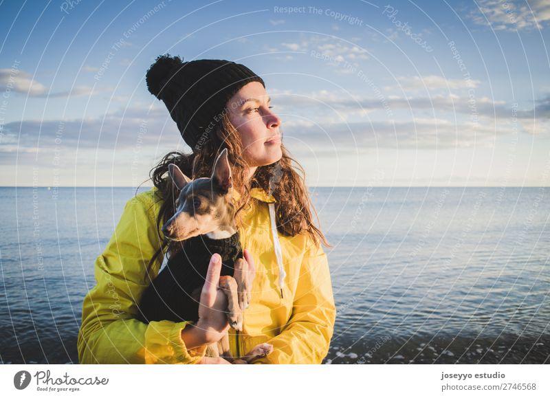 Frau mit ihrem kleinen Hund am Strand Lifestyle Erholung Ausflug Freiheit Sonne Winter 30-45 Jahre Erwachsene Natur Tier Horizont Küste Jacke Mantel Hut