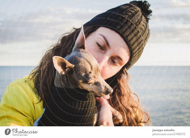 Frau mit ihrem kleinen Hund am Strand Lifestyle Erholung Ausflug Freiheit Winter Freundschaft 30-45 Jahre Erwachsene Natur Tier Horizont Küste Jacke Mantel Hut