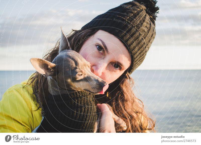 Frau mit ihrem Hund am Strand Lifestyle Erholung Ausflug Freiheit Sonne Winter Freundschaft 30-45 Jahre Erwachsene Natur Tier Horizont Küste Jacke Mantel Hut