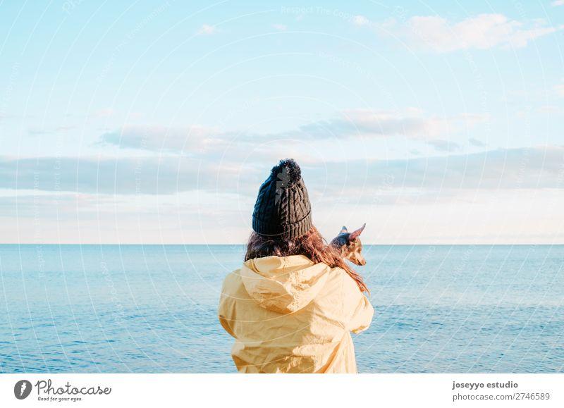 Frau mit ihrem kleinen Hund am Strand Lifestyle Erholung Ausflug Freiheit Winter Freundschaft Natur Tier Horizont Küste Jacke Mantel Hut Haustier Liebe gelb
