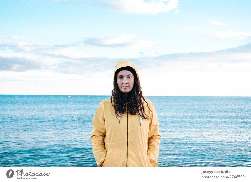 Frau am Strand mit gelbem Regenmantel und Hut Lifestyle Leben Erholung Ausflug Freiheit Sonne Winter Sport Sitzung 30-45 Jahre Erwachsene Natur Horizont Küste