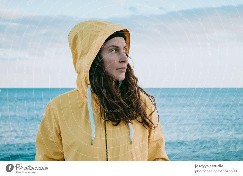 Frau am Strand in einem gelben Regenmantel Lifestyle Leben Erholung Ausflug Freiheit Sonne Winter Sport Sitzung 30-45 Jahre Erwachsene Horizont Küste Mode Jacke
