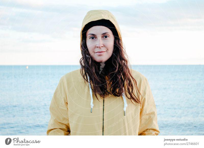 Frau am Strand im Winter Lifestyle Leben Erholung Ausflug Freiheit Sonne Sport Sitzung 30-45 Jahre Erwachsene Natur Horizont Küste Mode Jacke Mantel Hut Lächeln