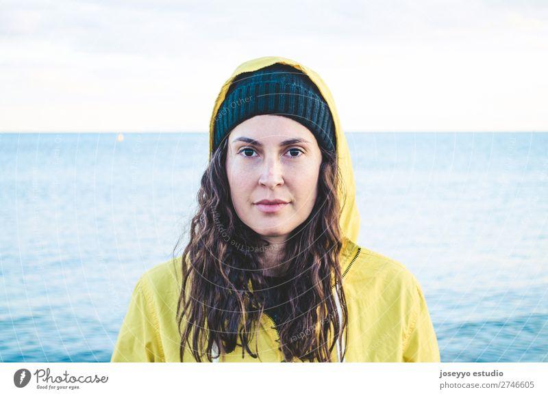 Porträt einer jungen Frau am Strand Lifestyle Leben Erholung Ausflug Freiheit Sonne Winter Sport Sitzung 30-45 Jahre Erwachsene Natur Horizont Küste Mode Jacke