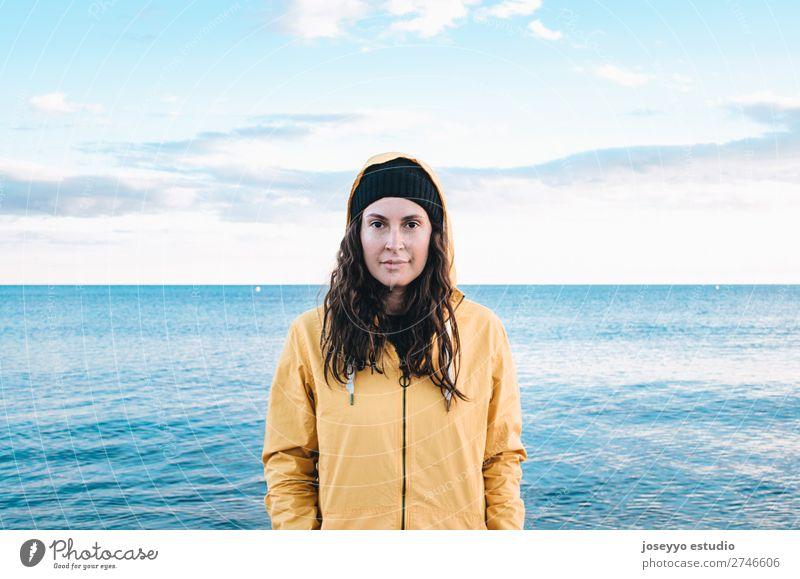 Junge Frau am Strand Lifestyle Leben Erholung Ausflug Freiheit Sonne Winter Sport Sitzung 30-45 Jahre Erwachsene Natur Horizont Küste Mode Jacke Mantel Hut