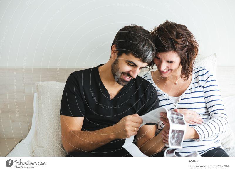 Glückliches schwangeres Paar beim Betrachten der Ultraschallbilder schön Leben Baby Frau Erwachsene Mann Eltern Mutter Vater Familie & Verwandtschaft Lächeln