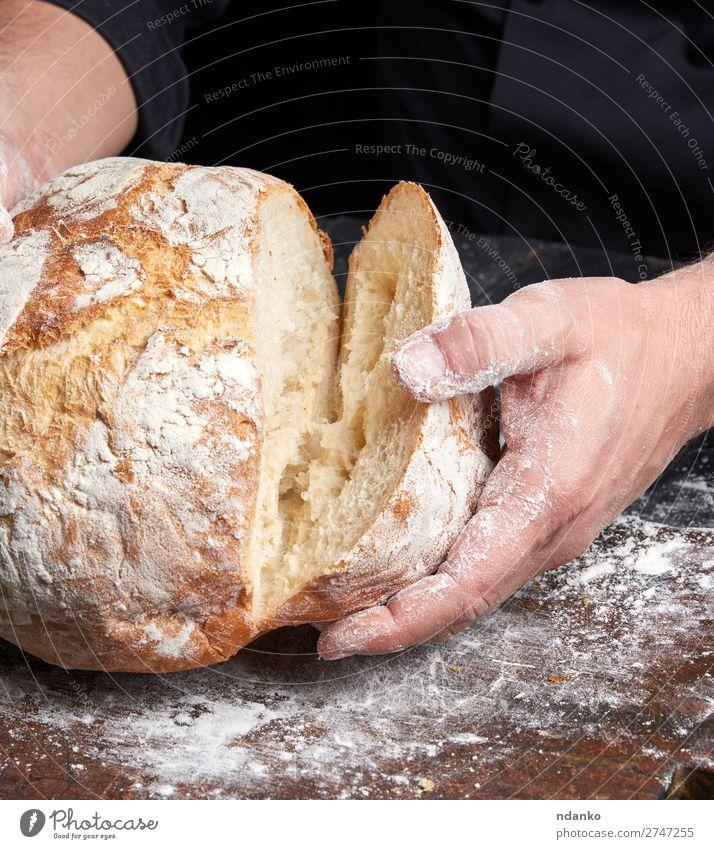 Koch in einer schwarzen Tunika hält frisch gebackenes Brot bereit. Ernährung Frühstück Tisch Küche Mensch Hand Finger Holz machen dunkel braun weiß Tradition