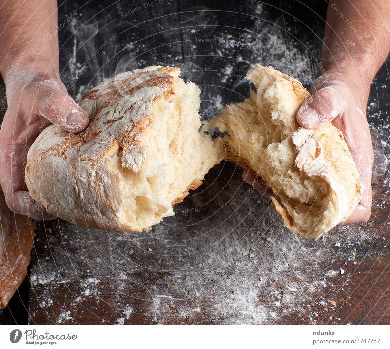 gebackenes Brot in zwei Hälften Ernährung Tisch Küche Beruf Koch Mensch Hand Finger Holz machen dunkel frisch heiß braun schwarz weiß Tradition Bäcker Bäckerei
