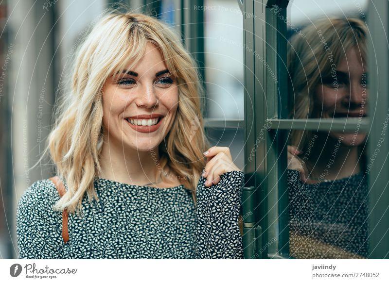 Lächelnde junge blonde Frau, die vor städtischem Hintergrund steht. Lifestyle Stil Freude Glück schön Haare & Frisuren Mensch feminin Junge Frau Jugendliche