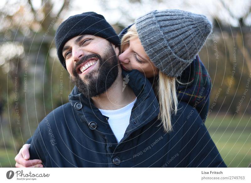 KNUTSCH - PAAR - WINTER - MÜTZEN Frau Erwachsene Mann Paar Partner 2 Mensch 18-30 Jahre Jugendliche 30-45 Jahre Mütze blond kurzhaarig Bart Lächeln Fröhlichkeit