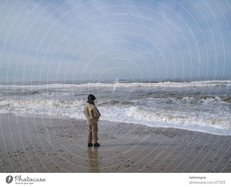 Frühjahr an der Nordsee Kind warm eingemummelt am Strand Wasser Sand Himmel