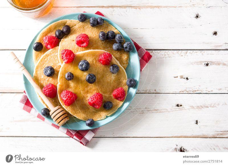 Pfannkuchen mit Himbeeren, Heidelbeeren und Honig süß Dessert Frühstück Blaubeeren Beeren blau rot backen Lebensmittel Speise Foodfotografie Teller vereinzelt