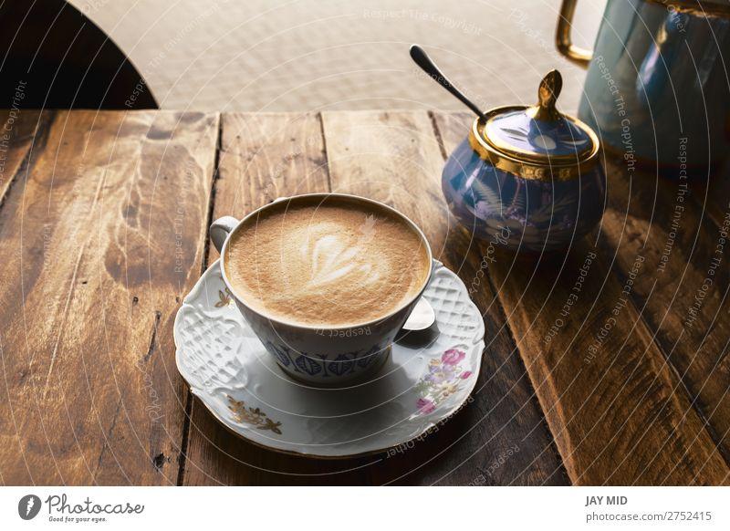 Cappuccino-Kaffee in klassischer Porzellantasse auf dem Holztisch Frühstück Getränk Espresso kaufen Tisch Restaurant Blume frisch heiß braun Farbe Tasse
