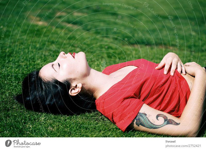 schöne Frau, die auf dem Rasen eines Parks liegt. Lifestyle Stil Sommer Garten Mensch feminin Junge Frau Jugendliche Erwachsene Körper Kopf Gesicht Arme Hand