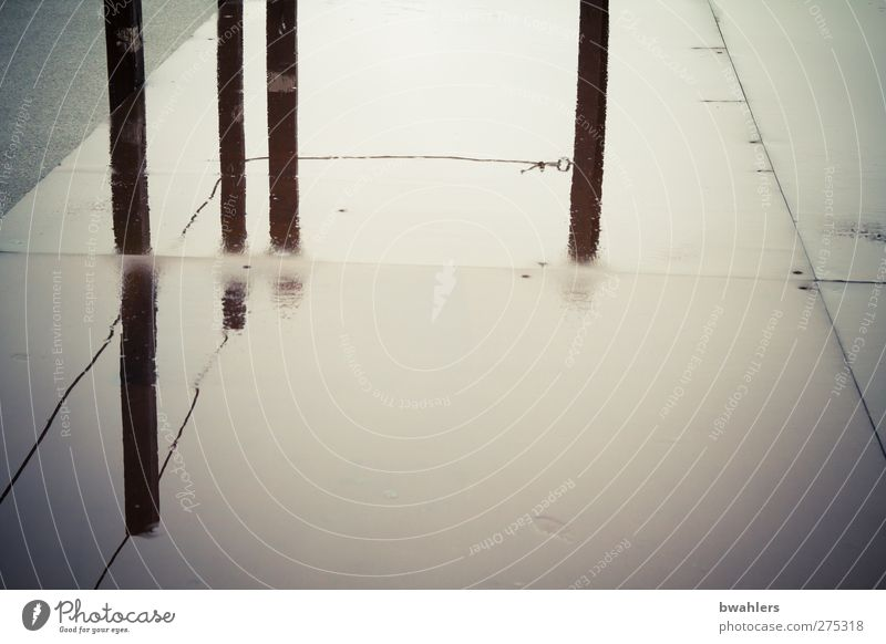 Spiegelung Platz nass grau schwarz Regenwasser Pfosten Gedeckte Farben Außenaufnahme abstrakt Textfreiraum unten Tag Kontrast Reflexion & Spiegelung