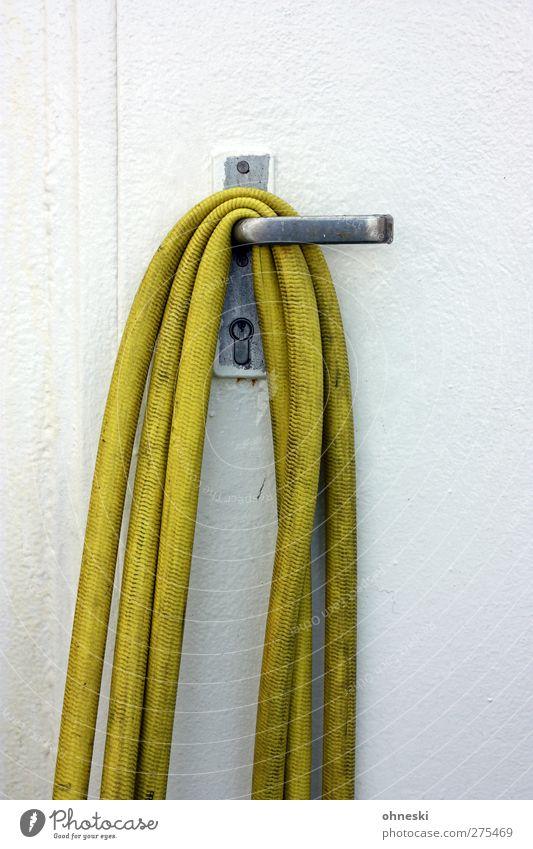 Abhängen Menschenleer Tür Schlauch Gartenschlauch Schloss Griff gelb weiß Ordnung Farbfoto Außenaufnahme Textfreiraum oben