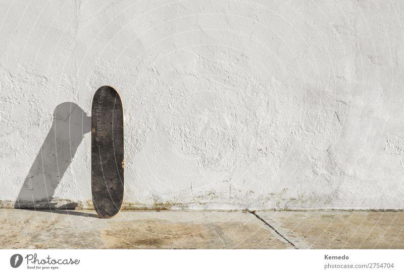 Skateboard auf einer verfallenen weißen Wand an einem sonnigen Tag. Lifestyle Leben harmonisch Erholung Freizeit & Hobby Reiten Abenteuer Freiheit Sommer
