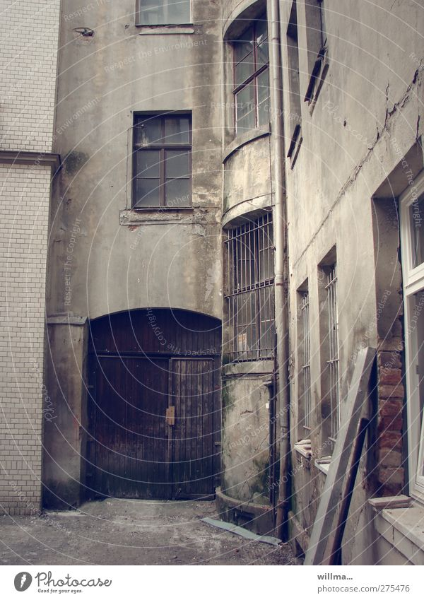 Der Hinterhof Menschenleer Haus Gebäude Innenhof dreckig dunkel grau Verfall Vergänglichkeit Wandel & Veränderung verfallen Neigung Fenstergitter Gitter Holztor