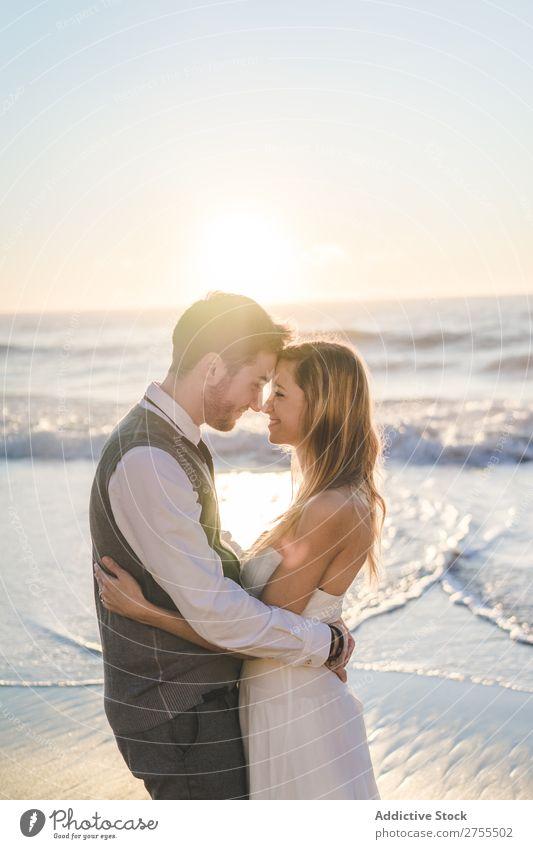 Zärtlich küssendes Brautpaar im Sonnenlicht Paar Hochzeit Strand umarmend Engagement Zufriedenheit Valentinsgruß Genuss verliebt Meereslandschaft stehen