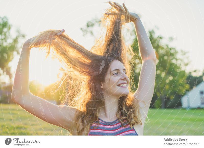 Mädchen, das im Sonnenlicht posiert und mit Haaren spielt. Frau spielerisch Park Behaarung Körperhaltung Freiheit Sommer Spielen Jugendliche Freude Natur