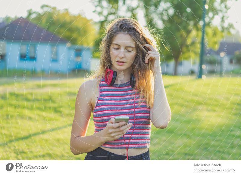 Stylisches Mädchen, das mit Gadgets posiert. Frau PDA Körperhaltung Erholung Sommer Natur Kopfhörer feminin Musik Zufriedenheit träumen Wiese Halt Gerät