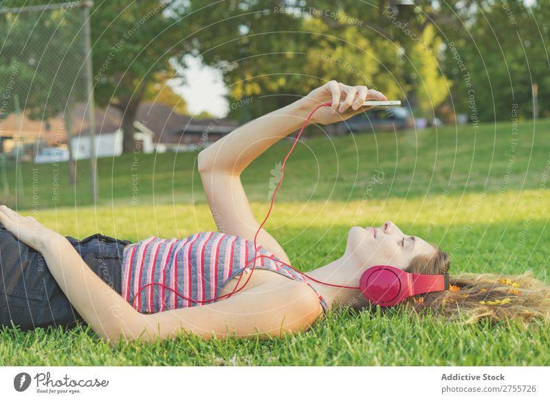 Mädchen mit Gadgets auf dem Rasen Frau Kopfhörer Erholung PDA feminin Musik träumen Blume Wiese Entertainment Schüler Park Sommer Freiheit Zufriedenheit Natur