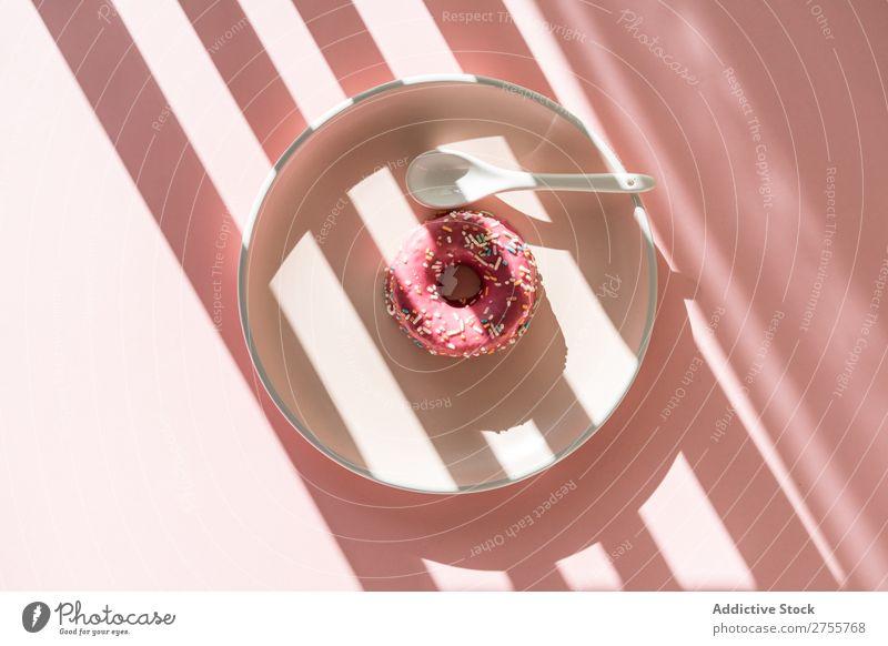 Süßer Doughnut in Sonnenstreifenform Krapfen minimalistisch rosa Sonnenlicht Streifen geometrisch Backwaren Teller Konfekt süß Hundefutter frisch Streusel
