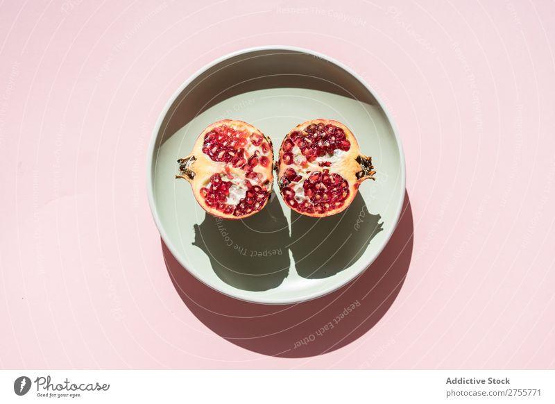 Granatapfelhälften im Sonnenlicht Hälften minimalistisch reif rot Frucht süß Kreativität saftig Abschnitt organisch Teller Schatten mehrfarbig Ordnung Speise