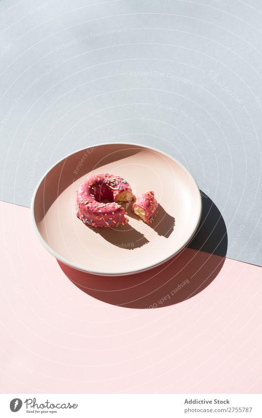 Köstlicher Doughnut auf Teller Zusammensetzung Krapfen mehrfarbig verglast minimalistisch geometrisch Symmetrie Konfekt Ordnung süß lecker Dessert Farbe rosa