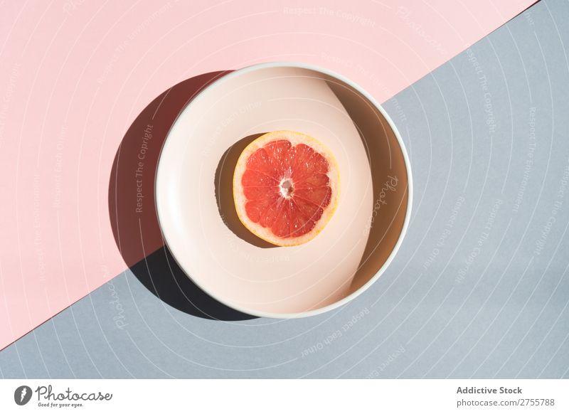 Grapefruit halb auf rundem Teller Ordnung Farbe Studioaufnahme Symmetrie geometrisch Scheibe exotisch süß Zusammensetzung Gesundheit minimalistisch frisch