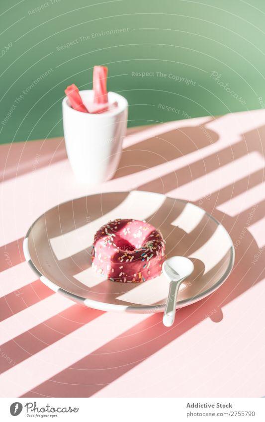 Bunte Donuts und Getränke im Sonnenlicht Zusammensetzung Krapfen trinken rosa lecker süß Dessert Streifen Backwaren Konfekt Kunst Teller Tisch Schatten Tasse