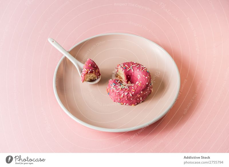 Süßer rosa Doughnut auf Teller Krapfen beißen Studioaufnahme lecker Dessert Kunst süß Spielfigur Süßwaren Feinschmecker Ernährung Kreativität Essen Löffel