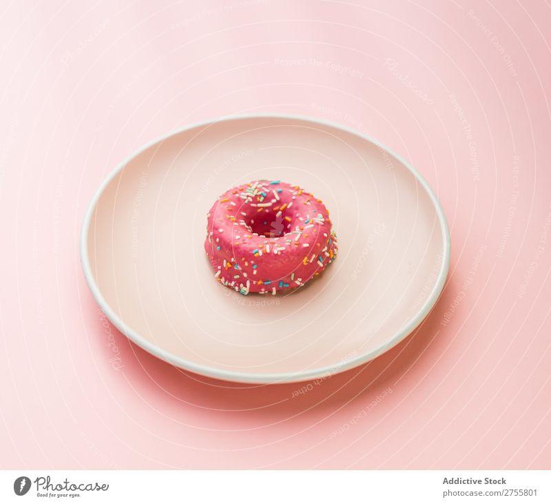 Süßer rosa Doughnut auf Teller Krapfen minimalistisch süß Symmetrie Studioaufnahme Lebensmittel Backwaren Kunst Dessert Bäckerei Essen zubereiten Gastronomie