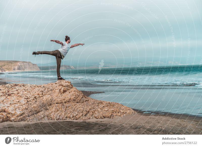 Der Mensch balanciert auf Stein auf See. Küste Mann Jugendliche Meer Gleichgewicht Yoga