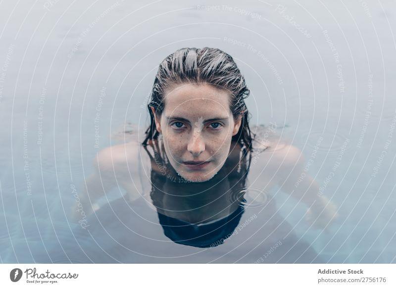 Frau, die auf die Kamera im Wasser schaut. lügen Schwimmsport Gesicht Blick in die Kamera auf den Kopf gestellt Schwimmbad Mensch Sommer blau